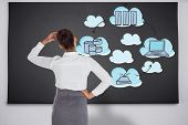 Businesswoman scratching her head against black chalkboard with business technology doodle