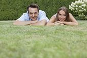 Portrait of smiling young couple relaxing on grass in park