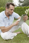 Young man using digital tablet while sitting on grass in park