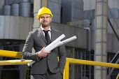 Portrait of confident young businessman holding blueprints outside industry