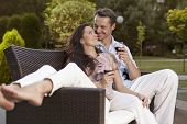 Romantic young holding wine glasses on easy chair in park