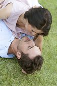 High angle view of romantic young couple lying together in park