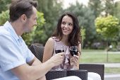 Loving young couple toasting red wine on chairs in park