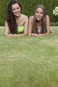 Portrait of attractive young female friends relaxing in park