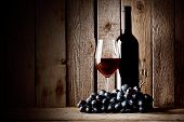 Bottle of red wine with a glass and grapes