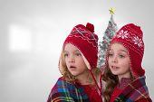 Cute girls under blanket against christmas tree in bright room
