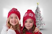Cute girls in hats against christmas tree in bright room