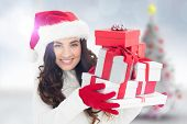 Festive brunette in santa hat holding pile of gifts against blurry christmas tree in room