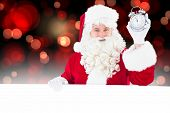 Santa claus holding alarm clock and sign against red glowing dots on black
