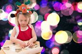 Festive little girl making cookies against twinkling yellow and purple lights
