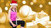 Fit festive young blonde measuring her thigh against orange vignette