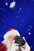 Santa is taking a picture against blue snowflake background