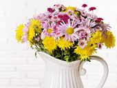 Beautiful flowers in pitcher on table on light background