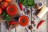 Tomato juice in glasses and fresh vegetables on cutting board on wooden background