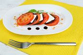 Eggplant salad with tomato and feta cheese on plate, on wooden background