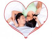 Beautiful loving couple lying in bed in heart-shaped frame