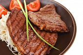 close-up of juicy sirloin beef with pasta tomatoes and green onion on dark dish isolated over white background