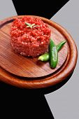 very big raw hamburger cutlet with sprouts and chilli pepper on wooden plate over black background