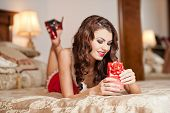 Young sexy Santa holding a gift, boudoir shoot. Attractive brunette with long hair