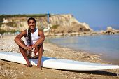 Young man sitting on surfboard by the sea edge