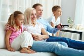 Happy family of four watching TV together on weekend
