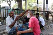 KOLKATA, INDIA - FEBRUARY 09, 2014: Street barber shaving a man using an open razor blade on a street in Kolkata, West Bengal, India