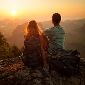 Couple of hikers sitting on top of the mountain and enjoying sunrise over valley