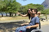 Disabled man in wheelchair and girlfriend in the park