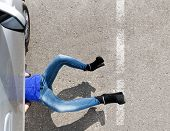 woman laying under her car