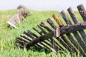 Fallen Wooden Fence On Green Earth