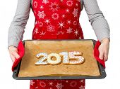 Woman wearing red apron holding home-made gingerbread cookies in shape of 2015 New Year digits on baking tray shot on white
