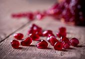 Red Pomegranate Seeds On Old Wooden Table