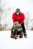 Mother and her son enjoy sledge in a snowy park