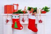 Mantelpiece with gifts and Christmas decoration on brick wall background