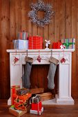 Fireplace with gifts and Christmas decoration on wooden wall background