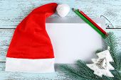 Santa red hat with fir-tree branch, card and pencils on color wooden background