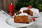 Slice of cake covered cream with Christmas decoration on table, on wooden wall background
