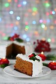 Slice of cake covered cream with Christmas decoration on table, on bright background