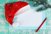Santa red hat with fir-tree branch, snowflakes, card and pencil on color wooden background