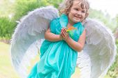 young beautiful angel child girl on natural green background
