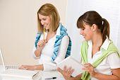 Estudante em casa - duas mulher com livro e Laptop