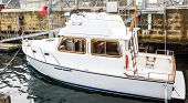 Small White Cabin Cruiser By Block Wall