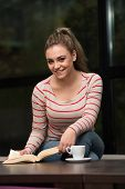 Smiling Young Student In Cafe Reading Book