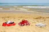 stock photo of nudism  - some swimsuits laying on the sand of a beach - JPG