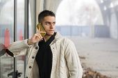 Handsome Young Man Standing Using A Mobile Phone