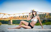 Portrait of young sexy brunette girl in swimsuit lying on the beach with a bridge in background