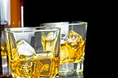 pic of whiskey  - whiskey with ice in glasses near bottle on black background with reflection - JPG