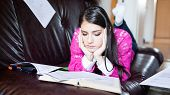 Attractive brunette woman student reading/ studying in her girly room