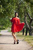 Beautiful woman in red dress walking summer street