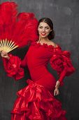 Sexy Woman traditional Spanish Flamenco dancer dancing in a red dress with a red fan